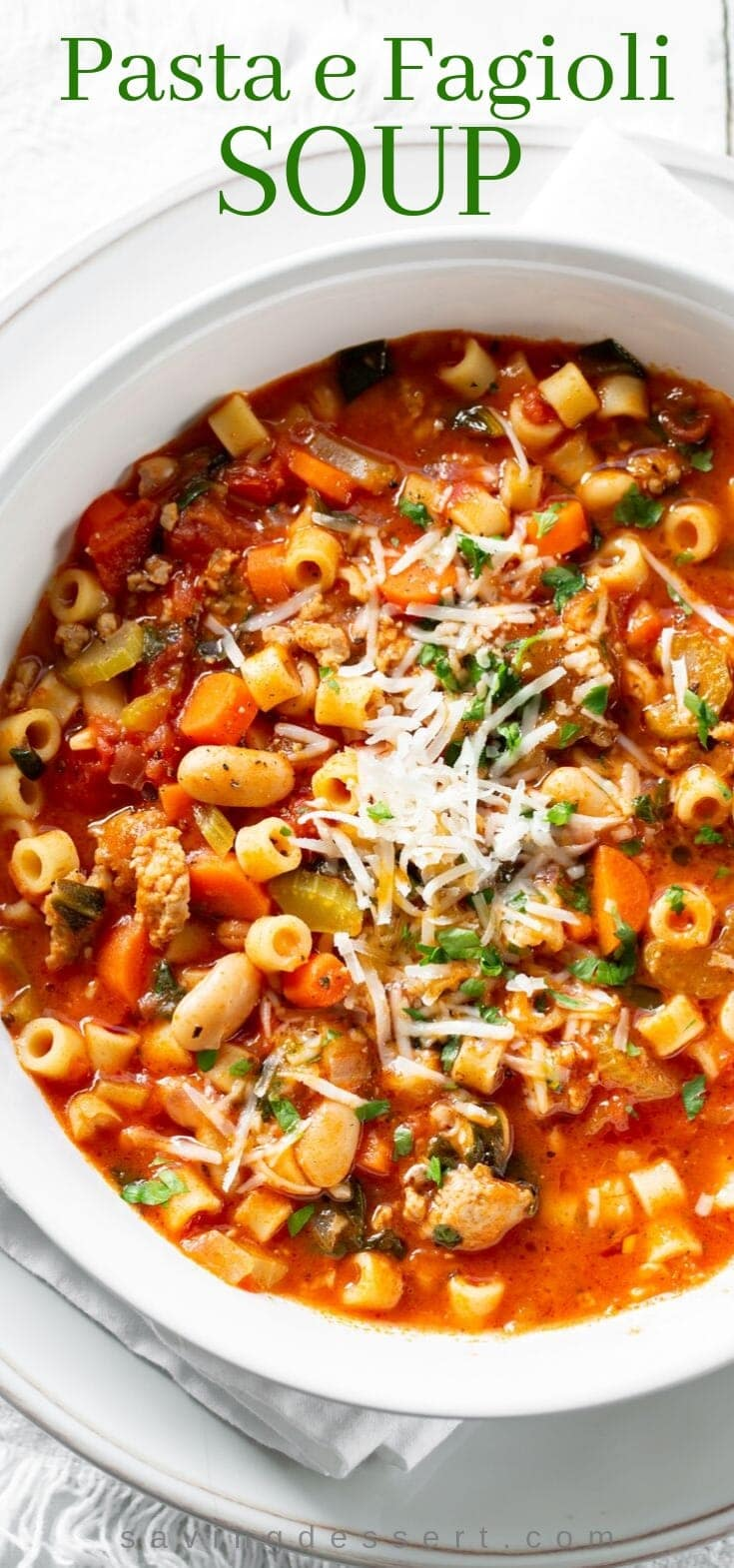 A big bowl of Pasta e Fagioli soup with Italian sausage and beans garnished with parsley and Parmesan