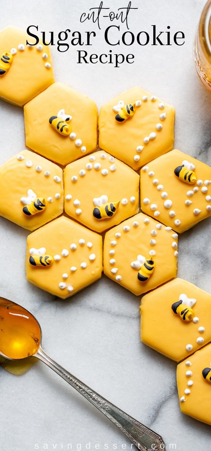 Sugar cookie recipe cut into hexagonal shapes decorated with honey bees made of Royal icing