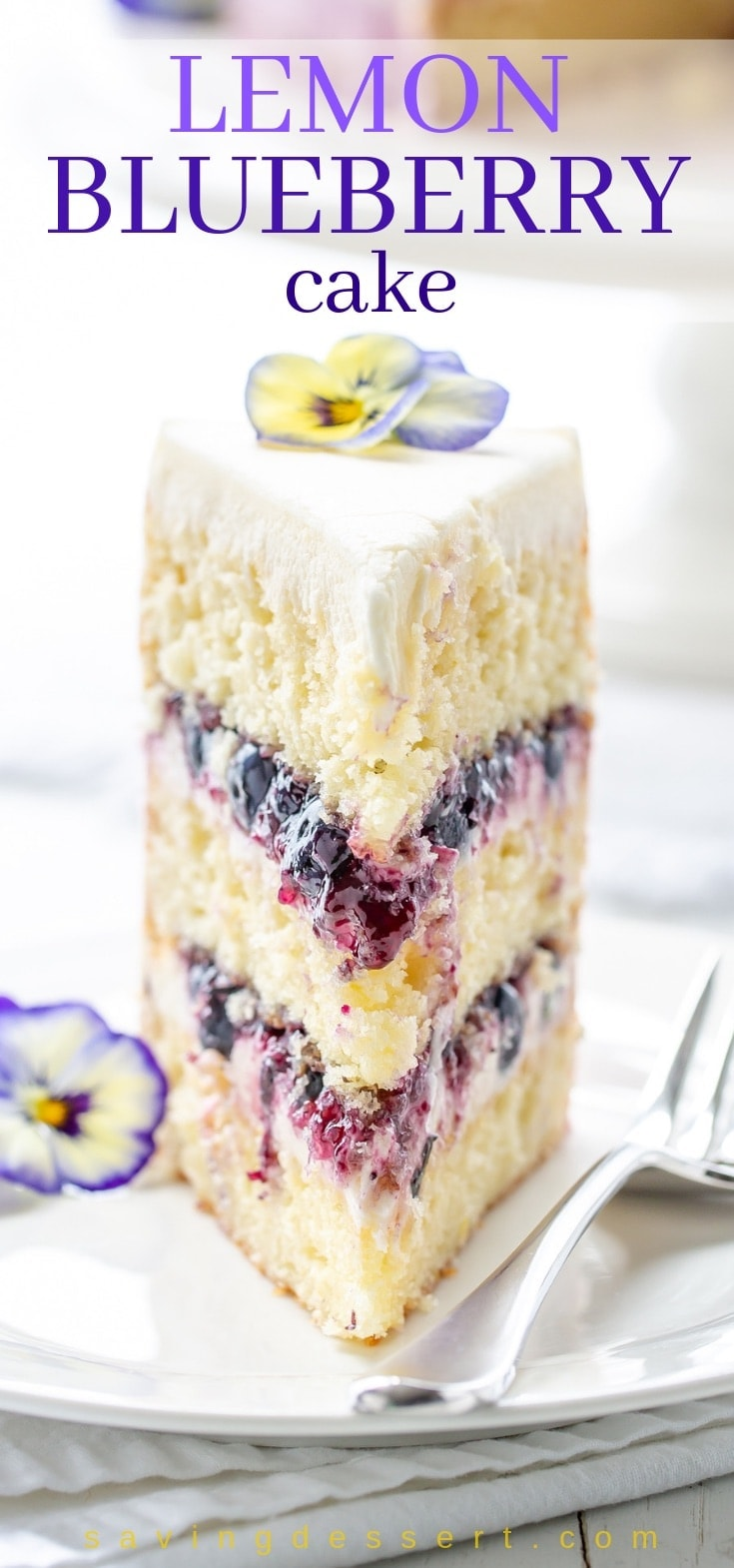 A slice of lemon blueberry cake topped with pansies