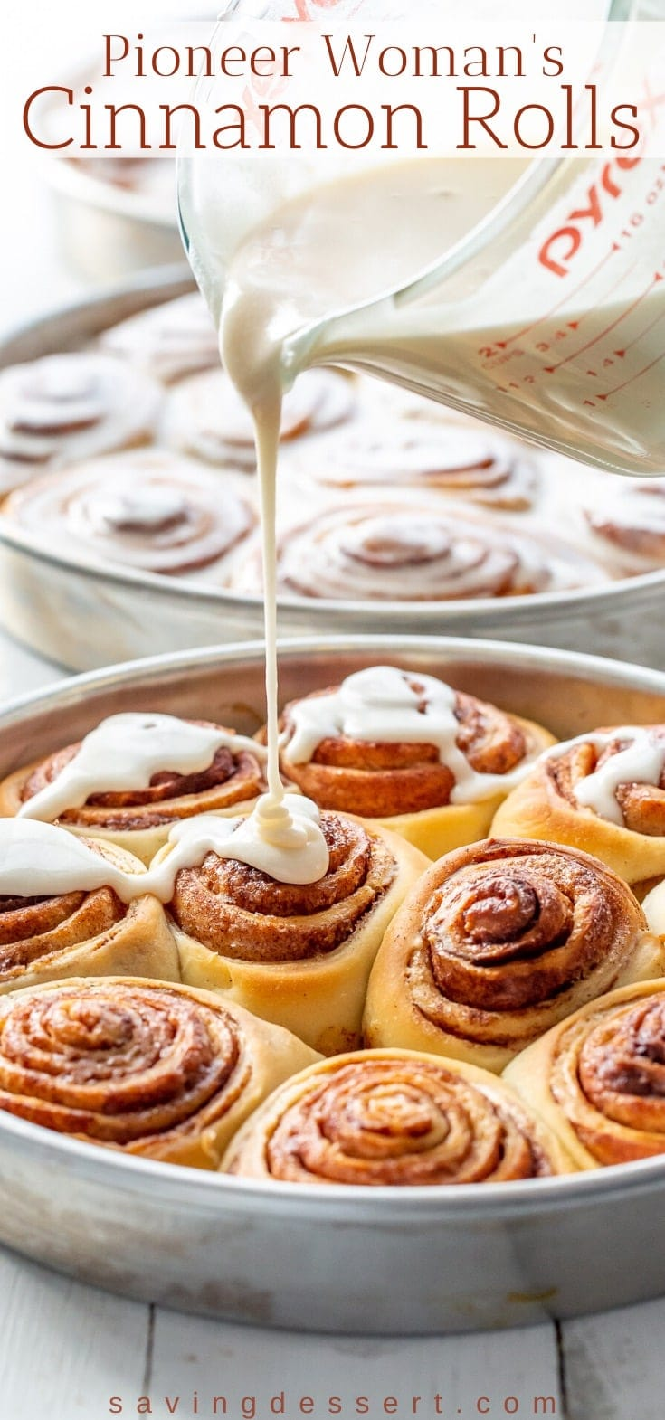 A pan of cinnamon rolls being drizzled with maple frosting