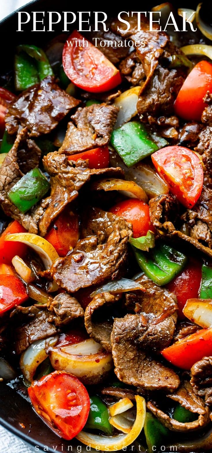 A skillet filled with thin sliced steak, tomatoes, onions and green peppers