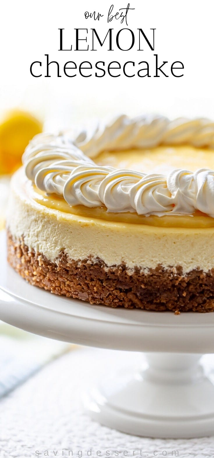 A side view of a lemon cheesecake with lemon curd on top decorated with whipped cream