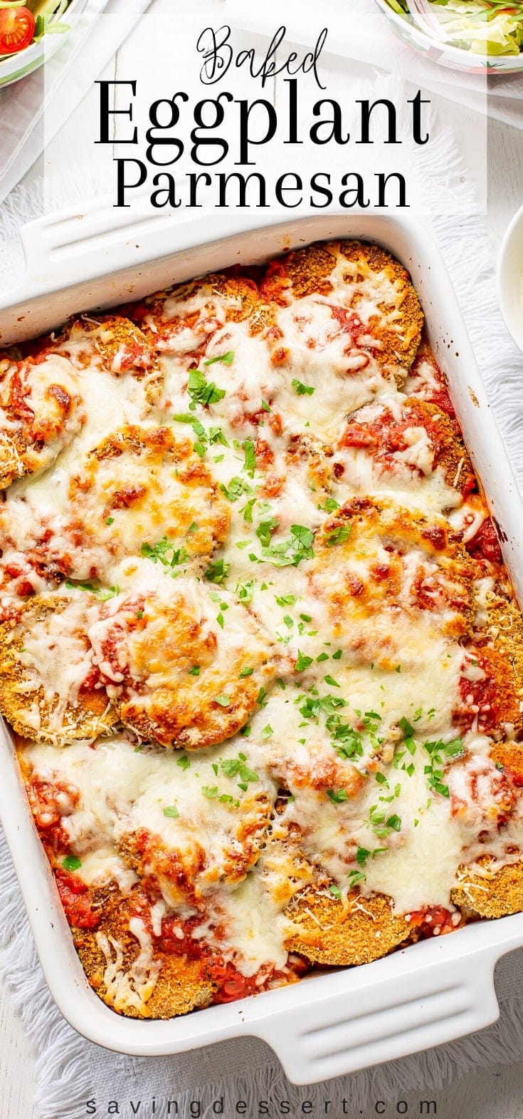 An overhead view of a casserole dish with hot baked eggplant Parmesan.