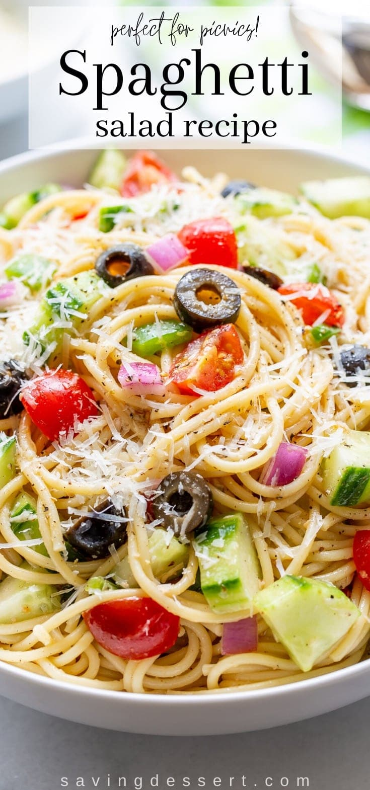 A bowl of spaghetti with red onion, olives, cucumbers and tomatoes tossed in an Italian dressing