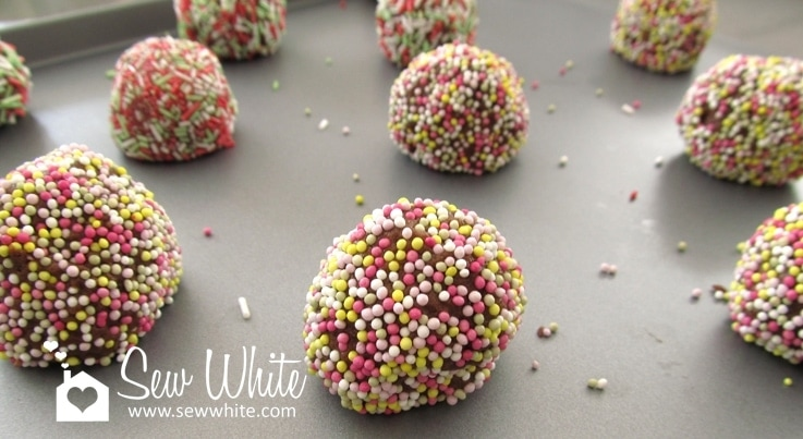 cookie dough balls covered in sprinkles ready to bake