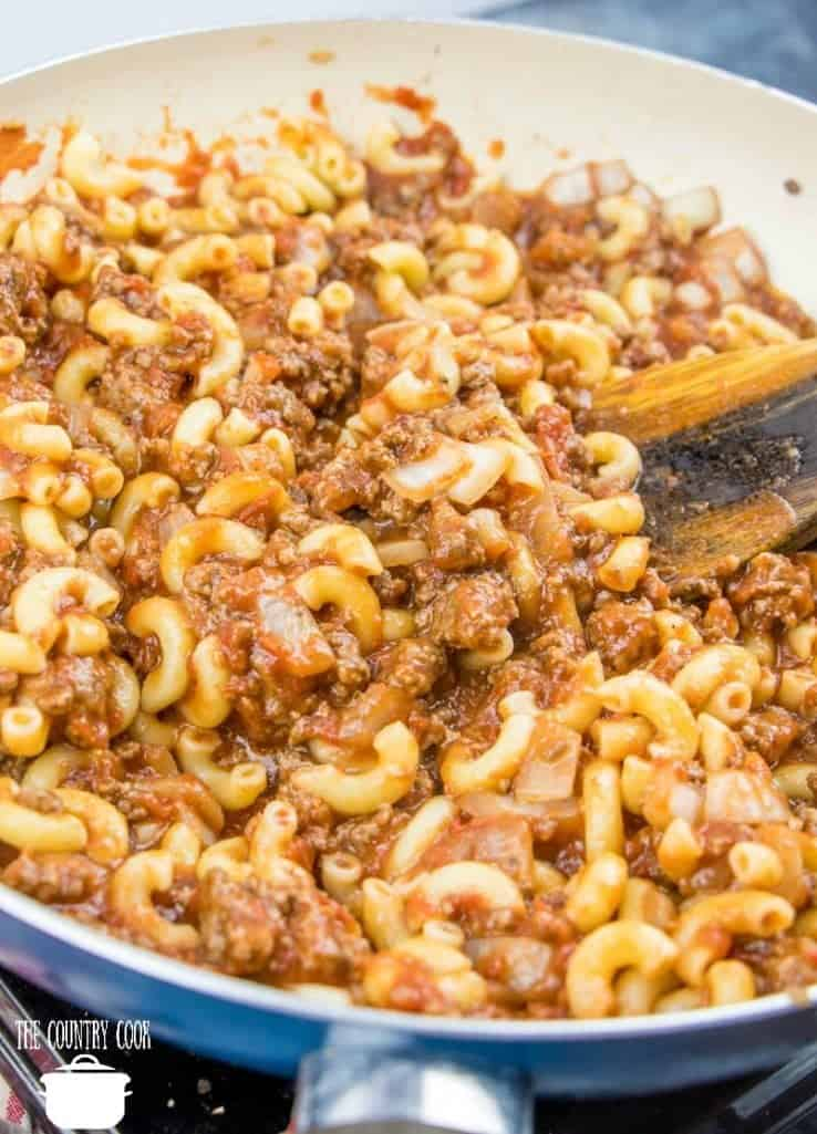 cooked macaroni noodles added to tomato sauce, crushed tomatoes, diced onion, garlic, Italian seasoning in a large skillet