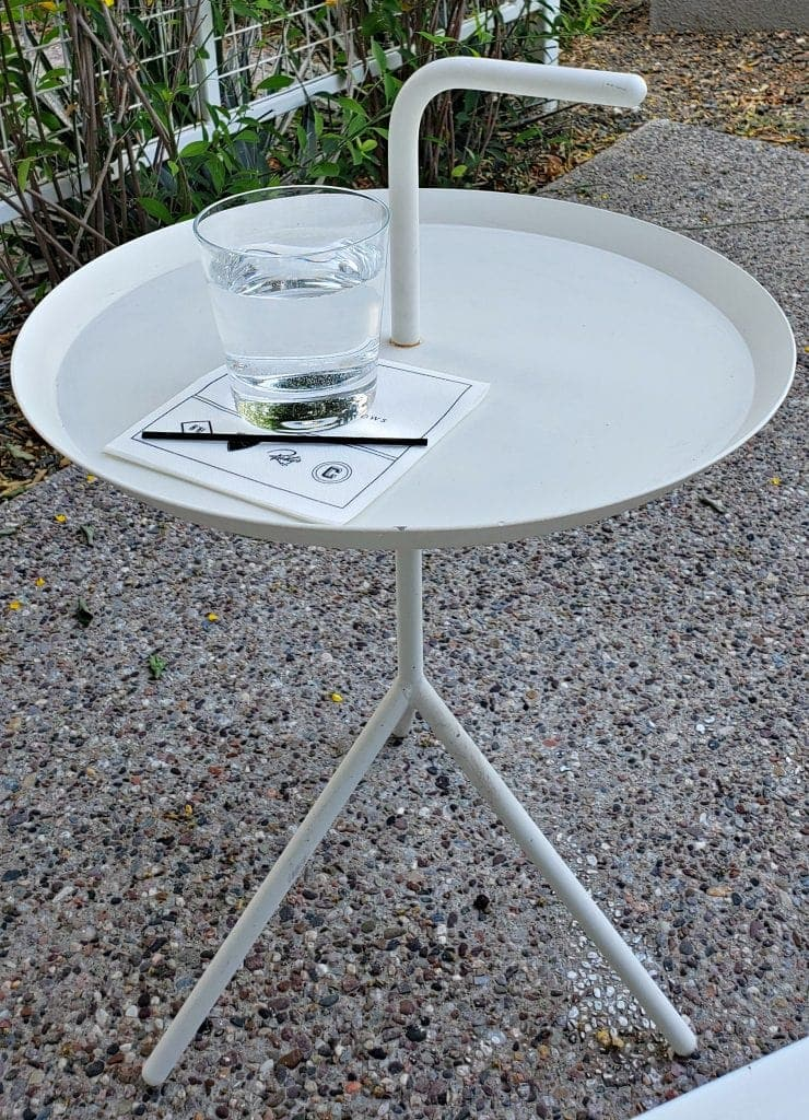 three-legged metal table with handle sticking up out of the center of the tabletop for easy repositioning
