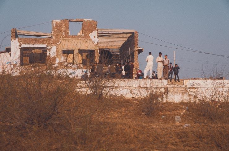 Nogle drenge hænger ud ved en forladt og faldefærdig bygning