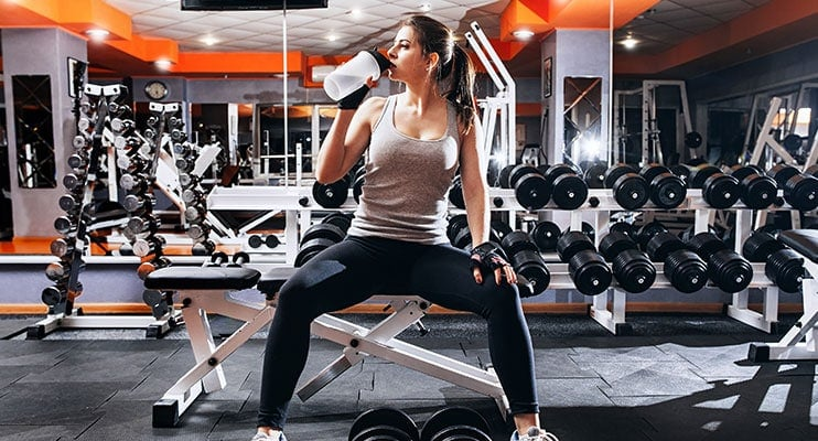 Fit Girl Sitting On Bench In Gym And Drinking Shake Protein