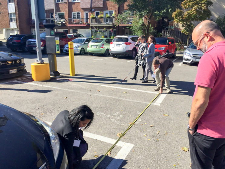 a man and a woman use a measuring tape to measure the width of an accessible parking space in an outdoor parking lot, a woman with a white cane walks by in the background