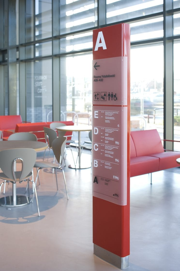 a bright red building directory stand