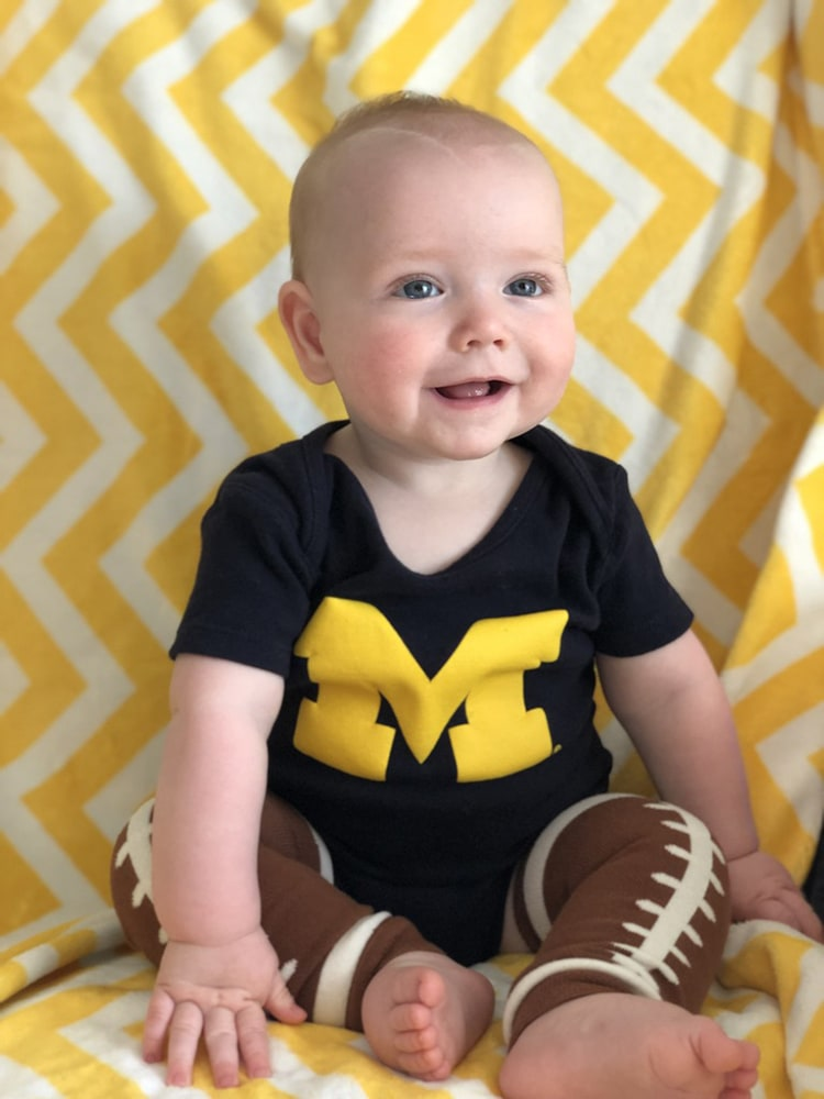 Hendrik Adams Vanderkaay—son of Alex, '08, MSE'10, and Elizabeth Dukes, '08—is all smiles in his Wolverine football gear.