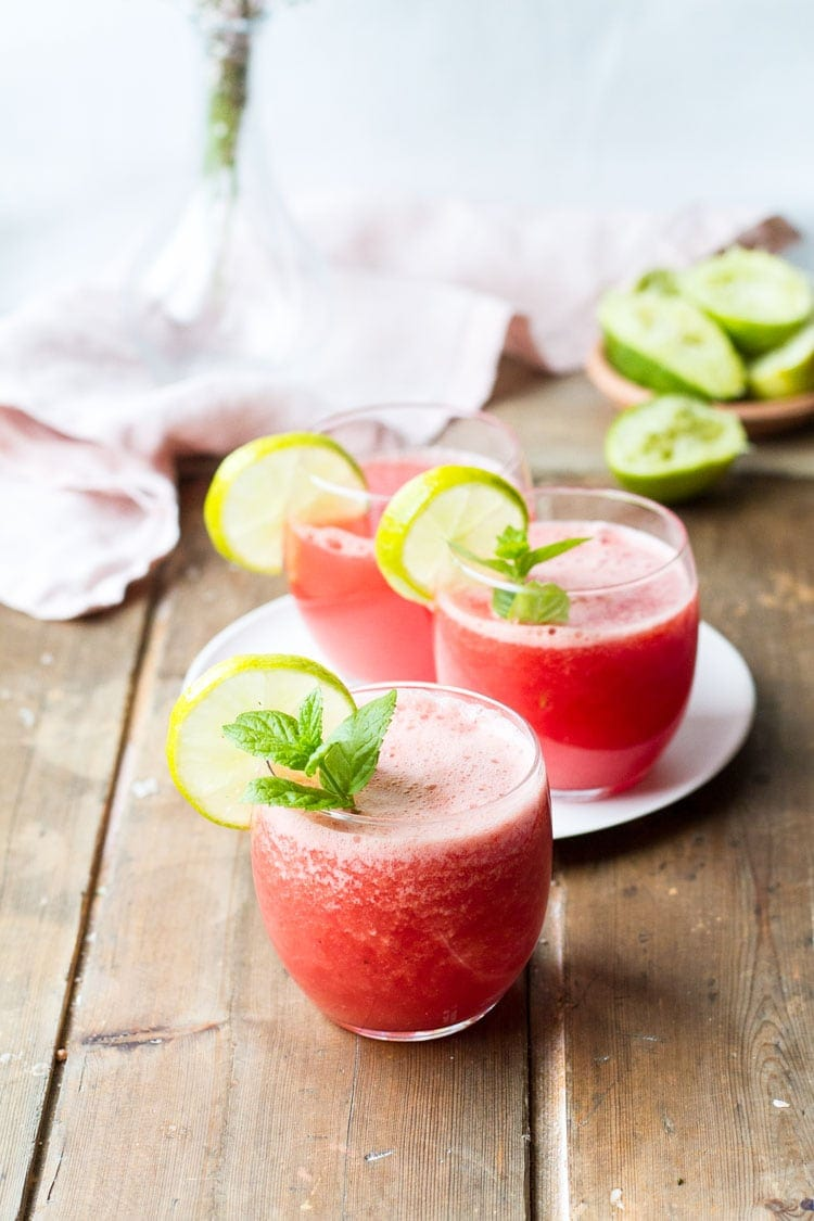 Three glasses with watermelon drink, mint garnish and lime wedges.