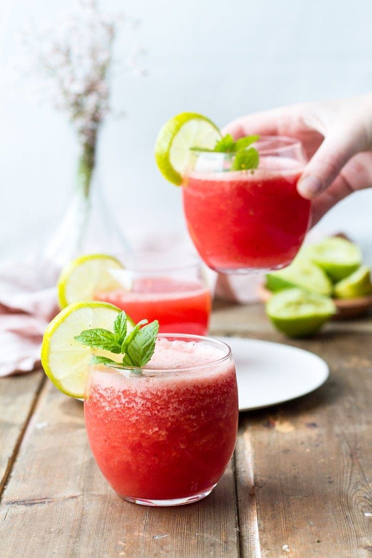 Three glasses with watermelon drink, hand holding one of the glasses.