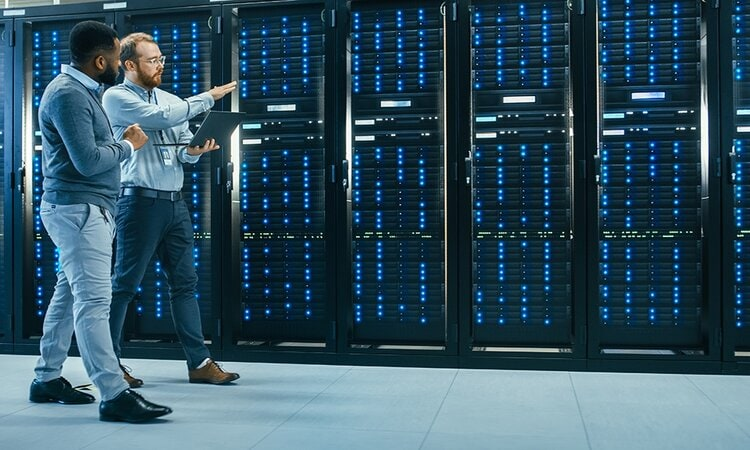 IT-Techniker mit einem Laptop und ein Ingenieur-Kollege unterhalten sich im Rechenzentrum, während sie neben den Server-Racks gehen. Sie führen Diagnosen oder Wartungsarbeiten durch.