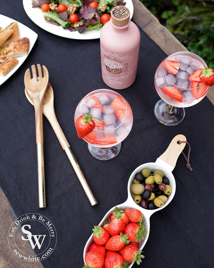 Table setting for a wimbledon party with navy blue table cloth, gin glasses with strawberries in and strawberries and olives on display.