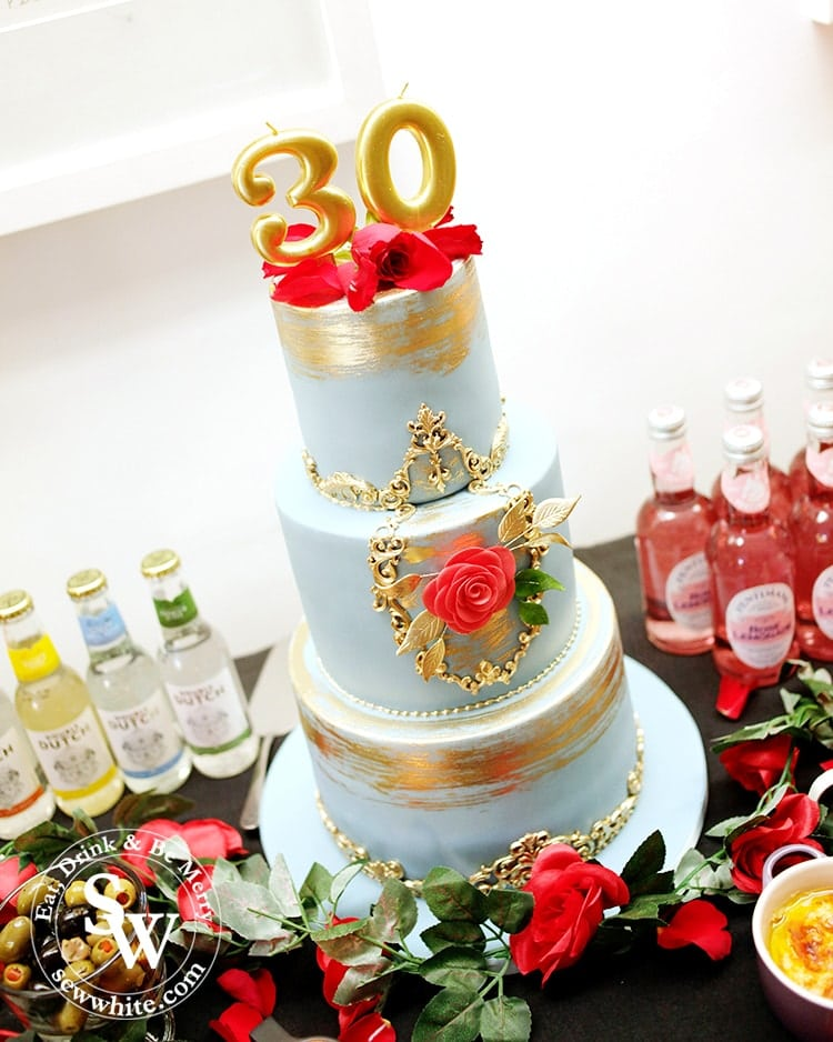 The Beautiful Beauty and the Beast inspired cake. Soft light blue cake with gold details, gold paint and topped with red roses and gold candles. Made by Cakes by Robin.