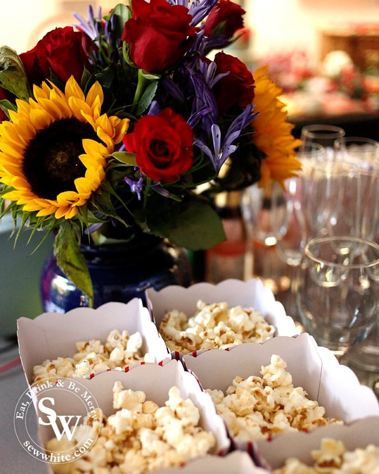 Sunflowers and roses in a dark blue vase with boxes of popcorn in front at the Beauty and the Beast Party.