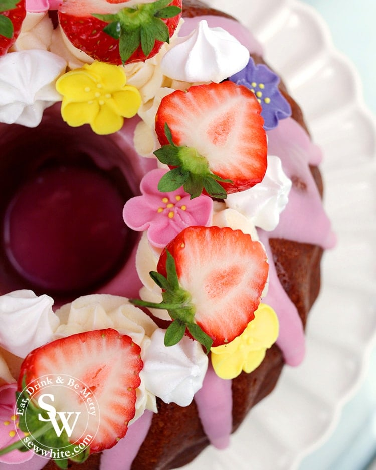 A close up of halved strawberries with mini meringue kisses and sugar flowers on bundt cake with pink icing.