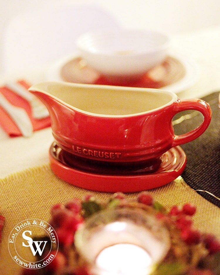 Gravy boat on the oval spoon rest in Christmas red from the Le Creuset collection