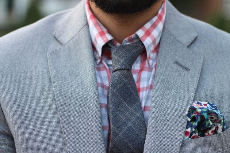 Серый костюм в сочетании с клетчатой рубашкой оранжевого цвета и трикотажного серого клетчатого галстука