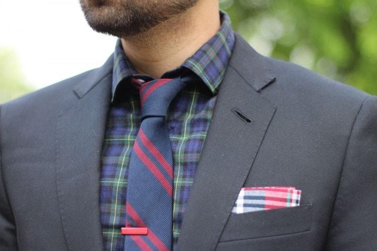 Темно-серый пиджак в сочетании с клетчатой рубашкой и полосатым галстуком