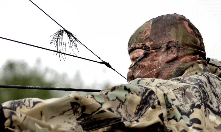 Bowhunter wearing camo skull cap at full draw