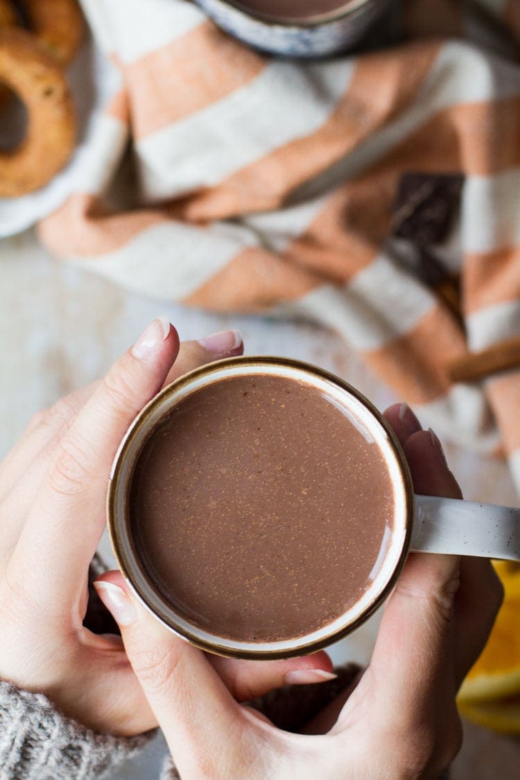 Hands holding a cup of hot chocolate.