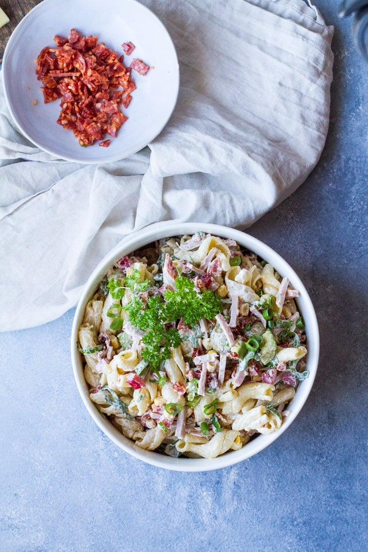 Creamy pasta salad in a white serving bowl, flatlay.