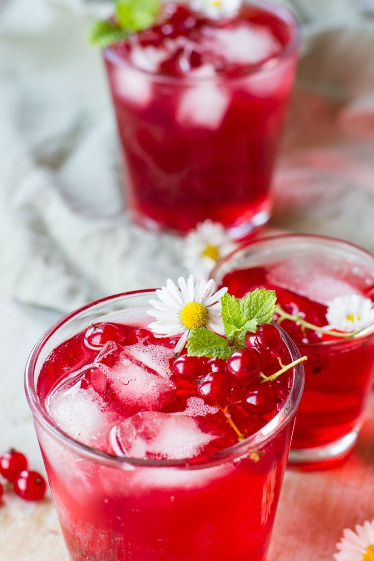 Three glasses with berry cordial and ice cubes. Garnished with flowers and mint leaves.