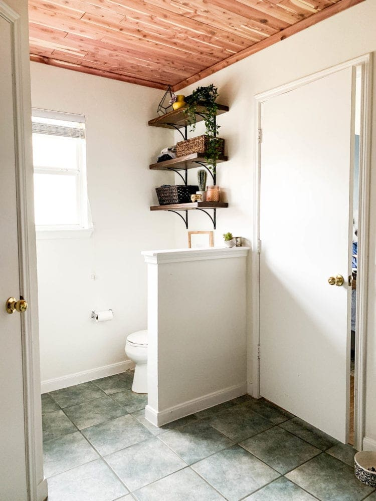 View of a bathroom - toilet and shelving with a cedar-planked ceiling