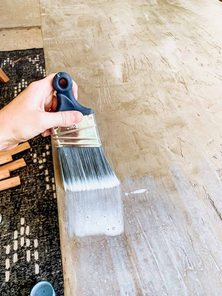 hand with a paintbrush applying concrete sealer