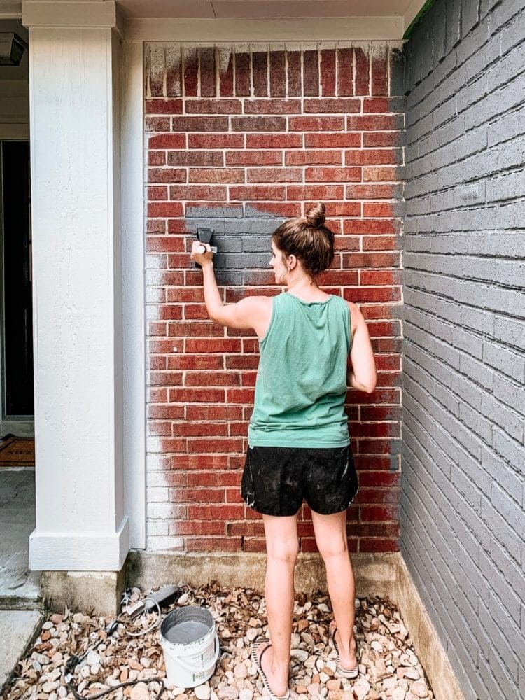 woman painting a red brick house with Romabio masonry paint in Navy Steel