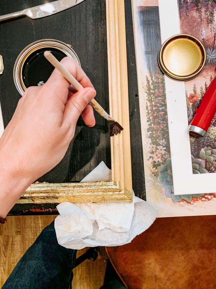 Woman's hand applying a gold leaf finish