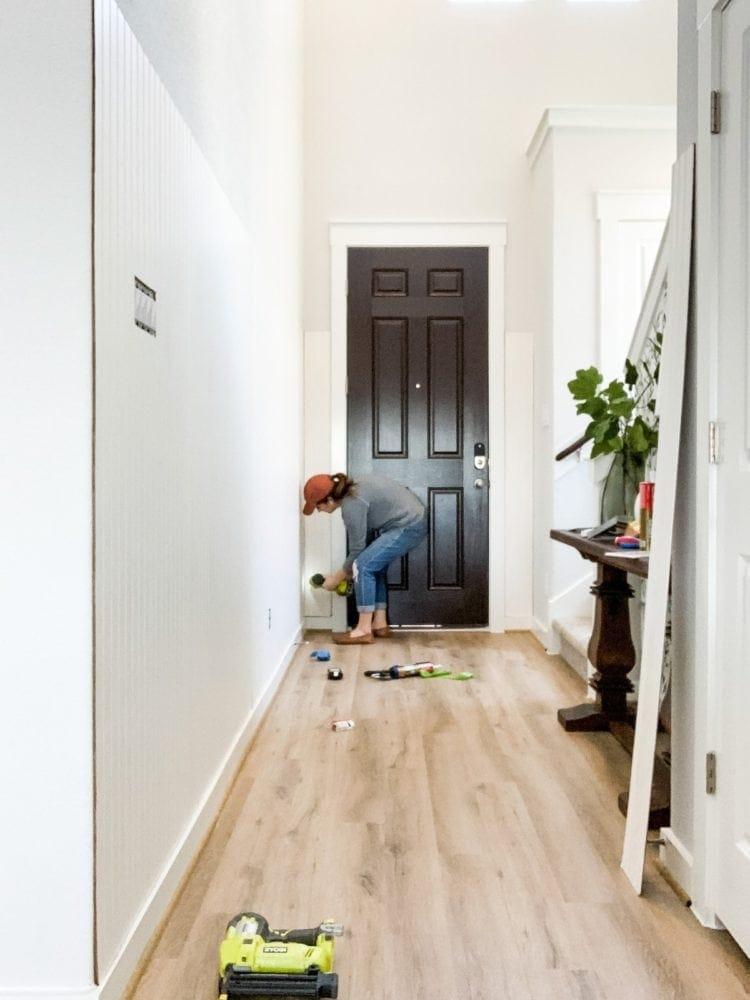 Woman using a nail gun to nail beadboard into wall