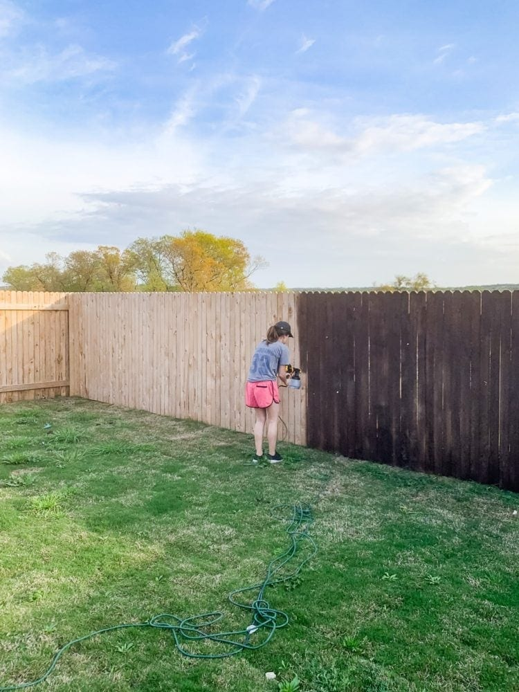Woman staining a fence using a paint sprayer