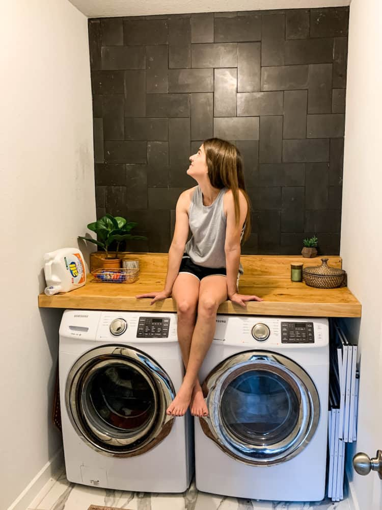 Woman sitting on a counter in a laundry room with a tiled basalt wall