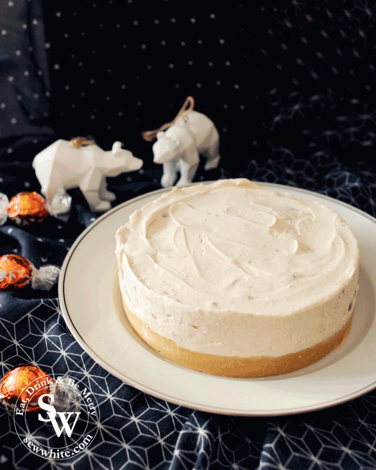 orange cheesecake surrounded by truffles and Christmas decorations.