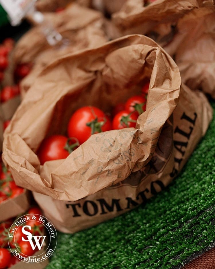 A brown paper bag of tomatoes on the market stall.