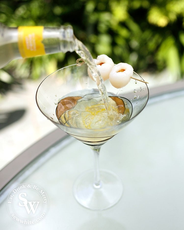 Lemon Lychee Martini being made. Double lemon mixer being poured over the top into the glass.