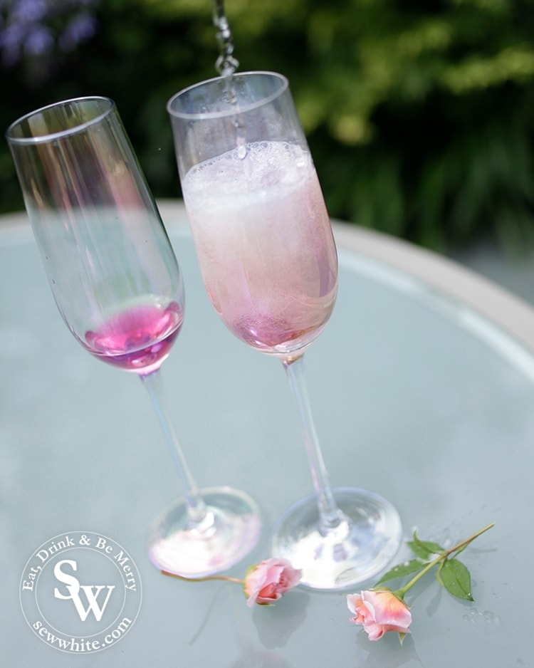 Pouring prosecco into the champagne glasses with elderflower and rose syrup for the Prosecco cocktail