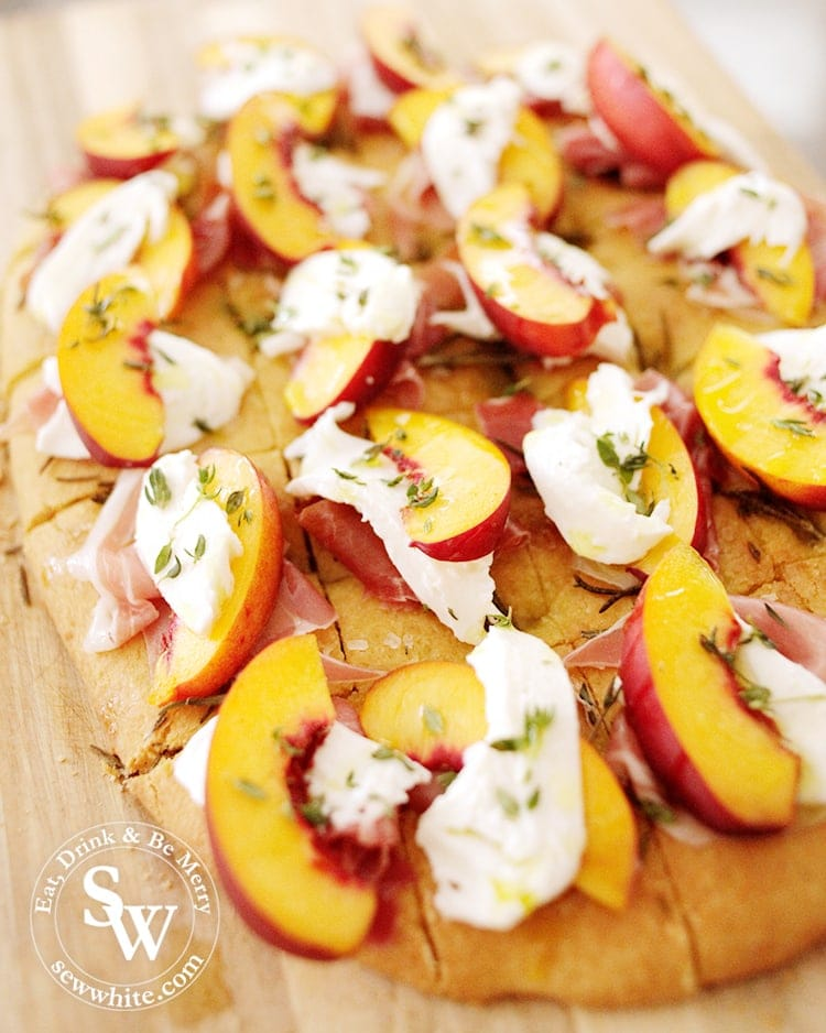 Homemade golden Focaccia cut up into pieces topped up with parma ham, peach slices, mozzarella and decorated with thyme and drizzled with olive oil. Easy Party Bites.