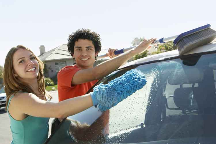Couple washing car together