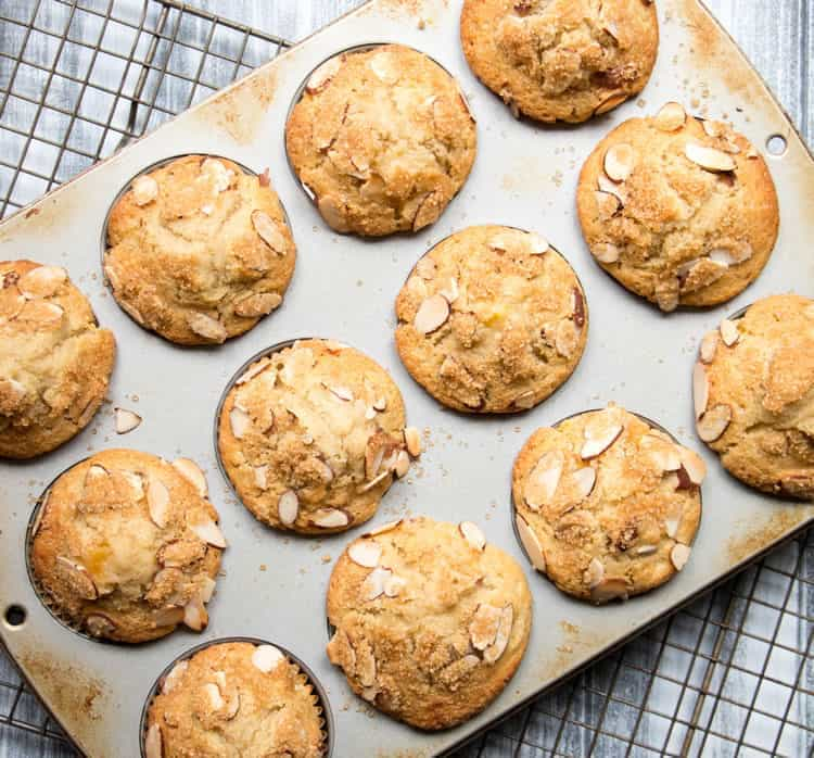 Peach Ricotta Olive Oil Muffins. Fluffy and full of fresh peaches, creamy ricotta and olive oil. A crunchy lid of almonds and raw sugar top them off!