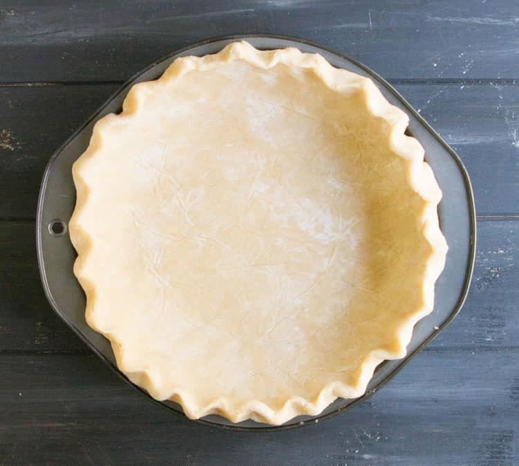 Easy All Butter Pie Crust in a pie pan fluted and ready for baking from themerchantbaker.com