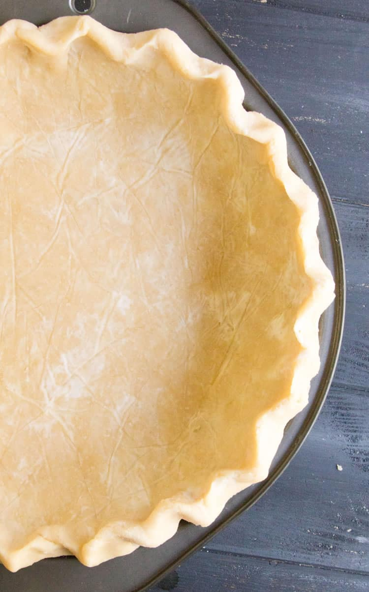 Easy All Butter Pie Crust presented in a pie pan ready to bake from themerchantbaker.com