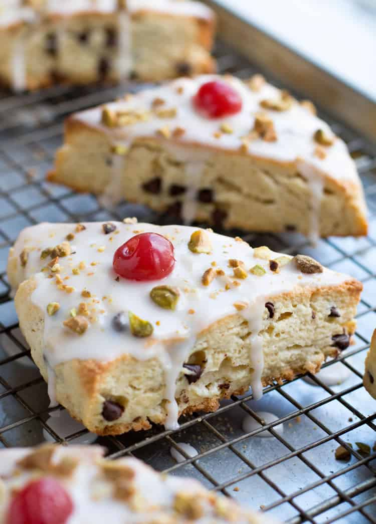 Chocolate Chip Ricotta Cannoli Scones are deliciously rich with butter and ricotta cheese, covered in a thin cherry vanilla glaze, then sprinkled with chopped pistachios and cherries!
