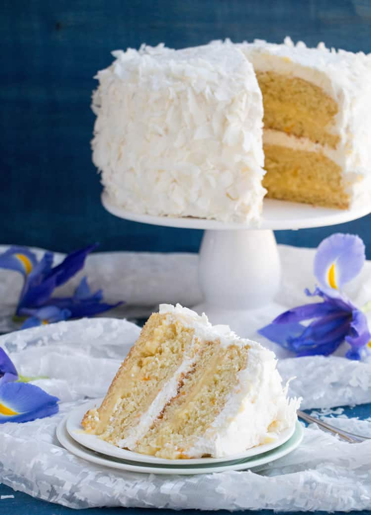 Mandarin Orange Pineapple Cream Cake. Layers of mandarin orange cake, filled with pineapple coconut pastry cream and covered in pineapple whipped cream and coconut chips. Perfect for Easter or Spring gatherings.