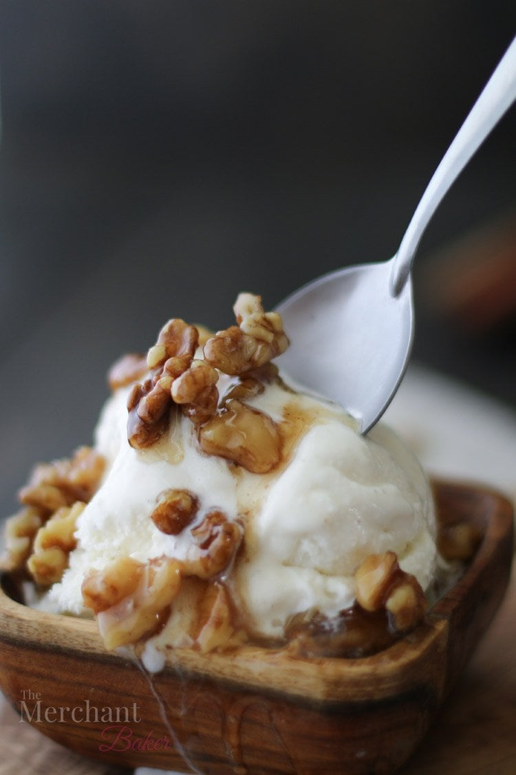 Spoon in a scoop of vanilla ice cream in a wooden bowl topped with walnut syrup