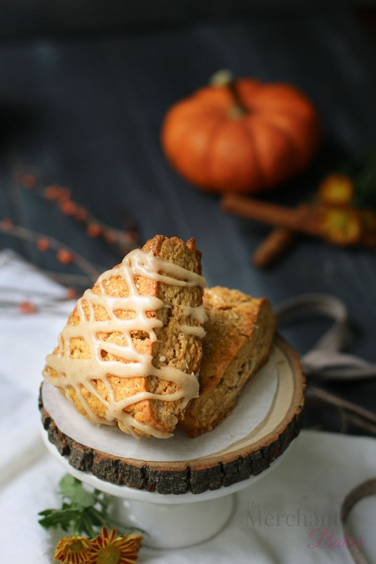Two of the best pumpkin scones displayed on a raw wood slab by themerchantbaker.com